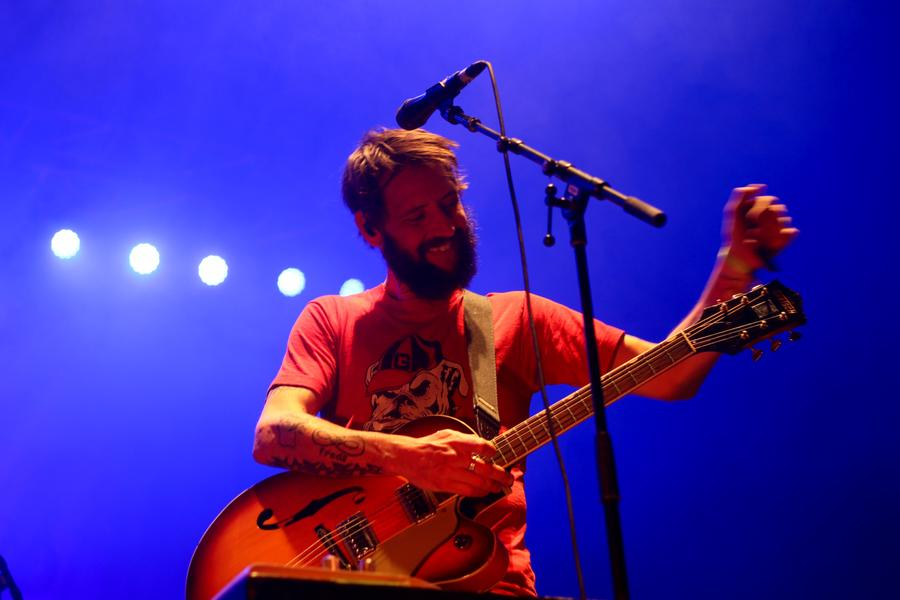 Lead singer Ben Bridwell stands at the microphone with his guitar.