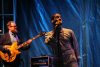 Leon Bridges stands at the microphone. The bassist stands behind him.