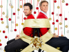 Mark Wahlberg and Will Ferrell sit while tied together by gift wrap ribbon and surrounded by ornaments.