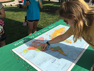 A college student is putting a pin on North America on a world map.