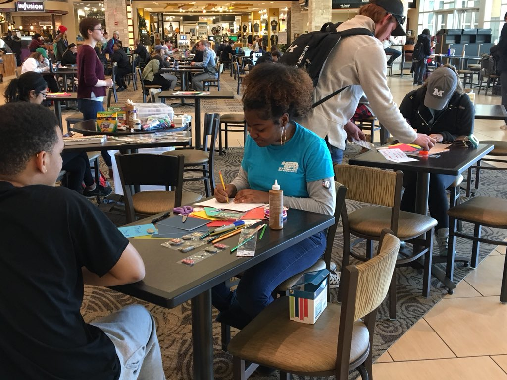 four students creating cards at tables in the MU Student Center
