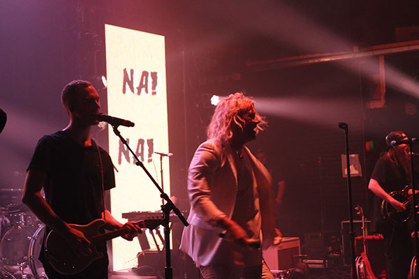 "The band stands in front of a video screen that reads ""Nap. Rap."""