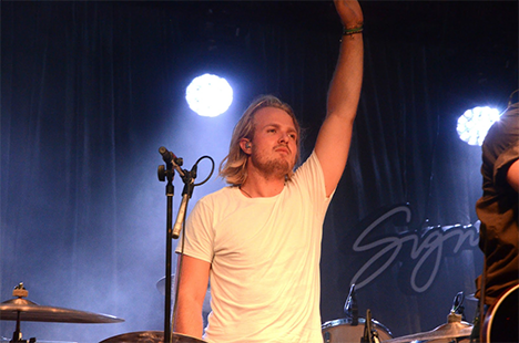 Sebastian Harris, the drummer, raises his fist.