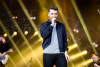 Sam Smith stands on a gold-lit stage.