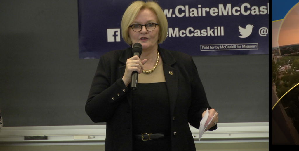 Sen. McCaskill holds a microphone and a piece of paper while she addresses students.