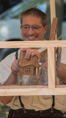 Second: a man building a small wooden house