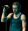 Macklemore stands at a microphone